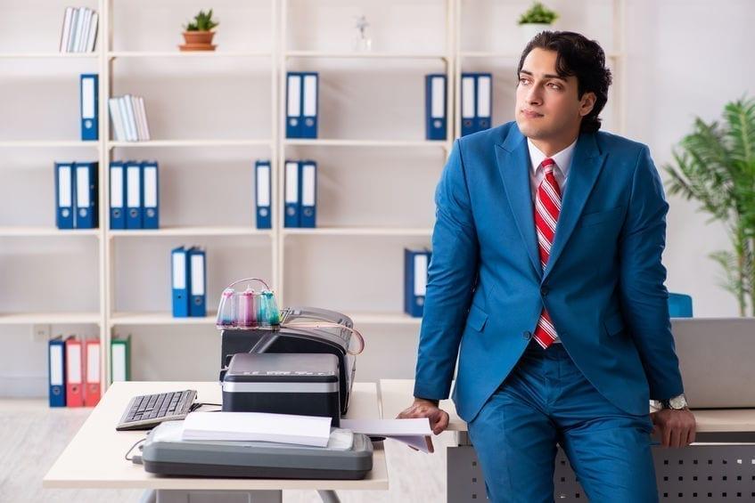 Young employee making copies at copying machine